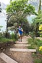 Italy, Trentino, woman running on stairs at Lake Garda - MRF001483