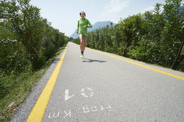 Italy, Trentino, woman running on road near Lake Garda - MRF001503