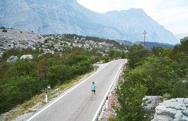Italy, Trentino, woman running on road near Lake Garda - MRF001510