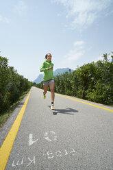 Italy, Trentino, woman running on road near Lake Garda - MRF001516