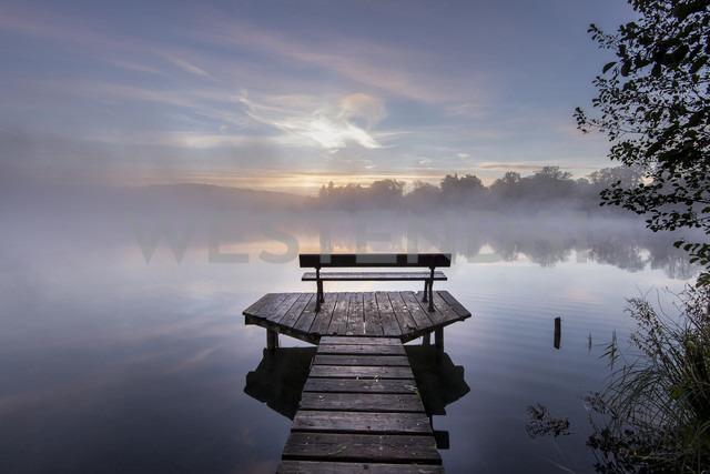 Germany, Bavaria, Wessling, Wesslinger See, boardwalk with wooden bench in the morning mist - MBOF000028