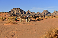 Algeria, Tadrart region, two touaregs walking through Sahara desert with their camels - ES001518