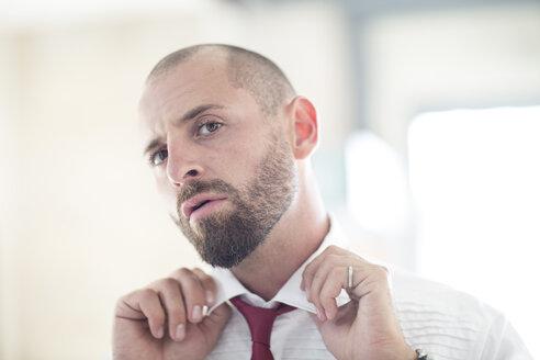 Portrait of man putting on his tie - ZEF002959