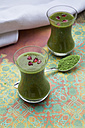 Two glasses of wheatgrass smoothie with pomegranate seeds - LVF002636