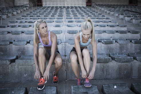 Two sportswomen sitting on grandstand of a stadium tying their shoes - ZEF004593