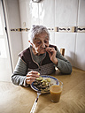 Aged woman eating fish and potatoes in the kitchen - RAE000012