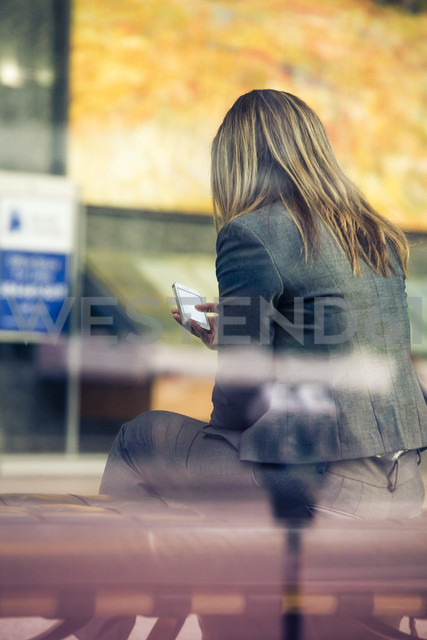 Canada, Vancouver, Blonde woman using smart phone - NG000202