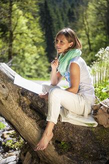 Austria, Altenmarkt-Zauchensee, woman drawing in the nature - HHF005062