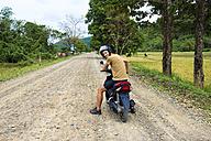 Philippines, Palawan island, man driving a motorcycle on a dirt road near El Nido - GEMF000009