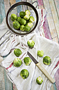 Brussel sprout in colander, kitchen towel and knife - SARF001277