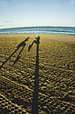 Spain, Valencia, shadow play of two persong on the beach - UUF003199