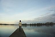 Germany, Roxheim, woman standing on wooden boardwalk at water - UUF003092