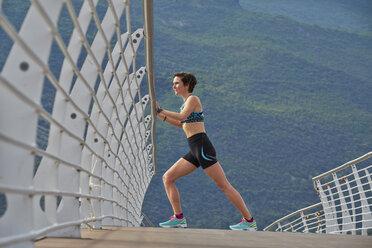 Italy, Trentino, woman stretching on bridge at Lake Garda - MRF001522
