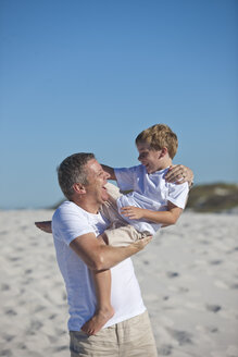 Playful father and son in sand - ZEF004769