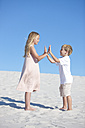 Brother and sister playing on a sandy beach - ZEF004772