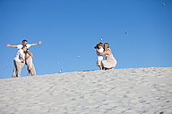 Mother and son taking a picture of father and children on a sandy beach - ZEF004774