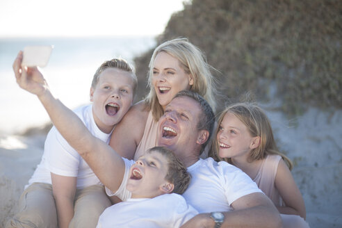 Happy family together on a beach taking a selfie - ZEF004777