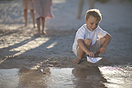 Boy playing with paper boat at a water pool on a sandy beach - ZEF004781