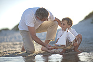 Father and son playing with a toy boat at a water pool on a sandy beach - ZEF004783
