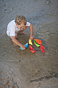 Boy playing with paper boats at a water pool on a sandy beach - ZEF004786