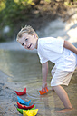 Boy playing with paper boats at a water pool on a sandy beach - ZEF004788