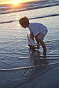 Boy playing with a toy wooden boat in the water at a beach - ZEF004796