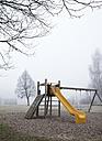 Austria, Mondsee, Autumn fog in park, playground - WWF003419
