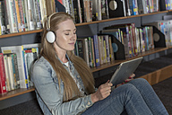 Female student with headphones and digital tablet sitting in a library - ZEF004359