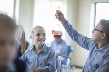 Pupil in chemistry class looking at round bottom flask - ZEF004977