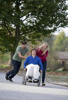 Young couple with friend sitting in wheelchair - WWF003653