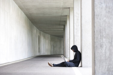 Hacker with laptop sitting in an underground car park - WWF003673