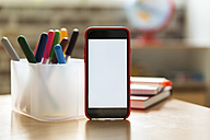 Smartphone on wooden table in children's room - MFF001409