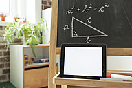 Tablet computer leaning at blackboard in children's room - MFF001413