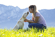 Austria, Mondsee, woman with Labrador Retriever on Alpine meadow - WWF003741