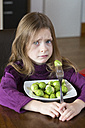 Unhappy little girl with plate of Brussels sprouts - SARF001297