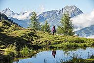 Austria, Altenmarkt-Zauchensee, young woman hiking in alpine landscape - HHF005072
