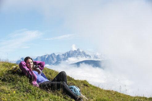 Austria, Altenmarkt-Zauchensee, young woman lying on alpine meadow - HHF005077