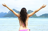 Philippines,Palawan, El Nido, woman with outstretched arms at Las Cabanas beach - GEMF000031