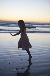 Little girl at beach dancing in evening twilight - ZEF002346
