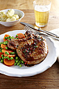 Pork chop with carrots, peas and boiled potatoes on plate - KSW001386