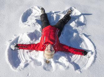 Austria, Tyrol, Pertisau, young woman making snow angel - MKFF000155