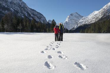 Austria, Tyrol, Pertisau, couple standing in winter landscape - MKFF000160