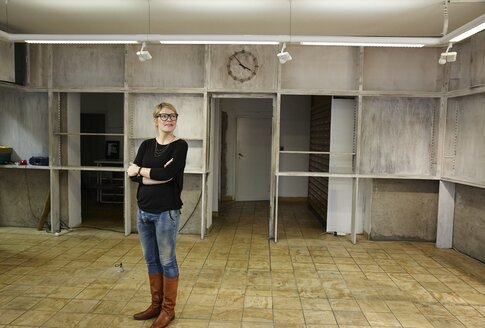 Woman standing in empty shop - EDF000121