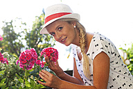 Young woman smelling at flowers in the garden - WWF003679