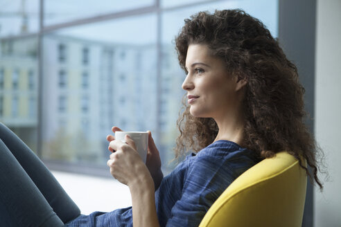 Young woman with cup of coffee looking out of window - RBF002311