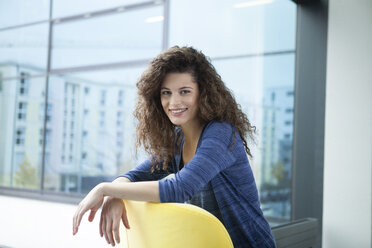 Portrait of smiling young woman at the window - RBF002314