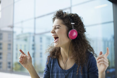 Screaming young woman wearing headphones at the window - RBF002317