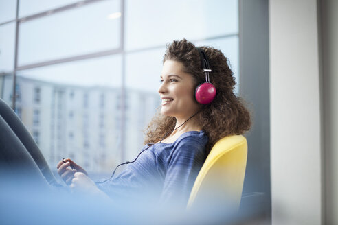 Smiling young woman wearing headphones at the window - RBF002323