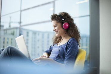 Smiling young woman wearing headphones and using laptop at the window - RBF002326