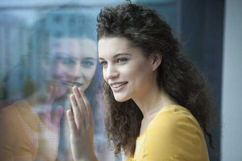Smiling young woman looking out of window - RBF002335